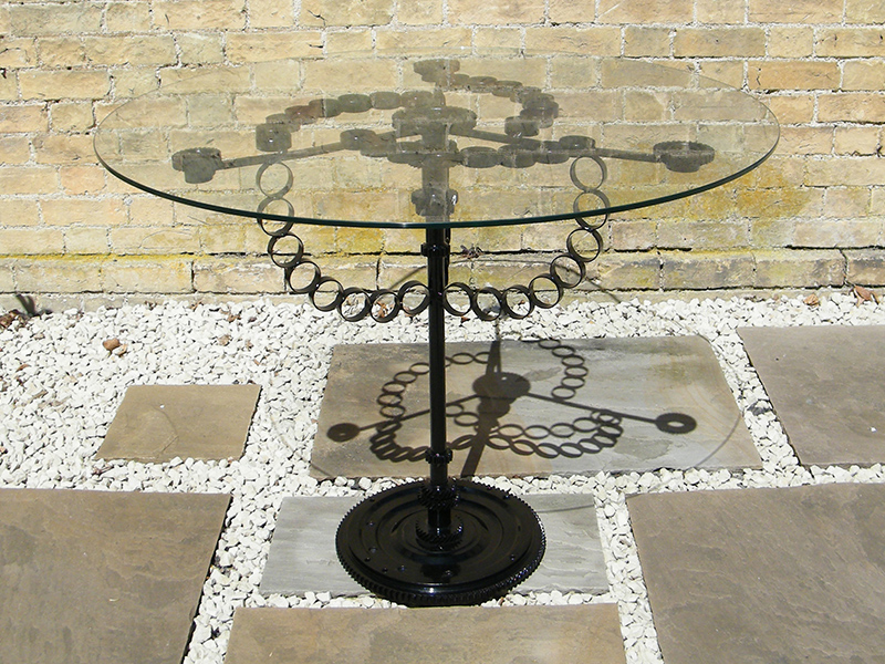 Glass table created from reclaimed steel and found objects